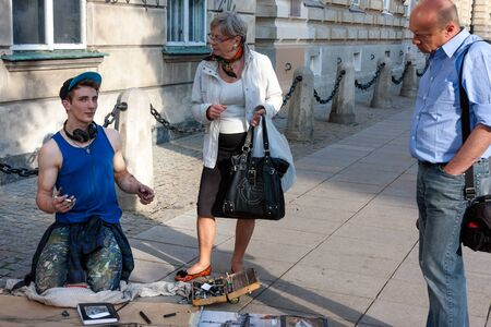Street artist painting and drawing, talking to tourists in Warsaw Stock Photo - 37711048