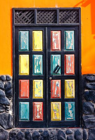 Door with colorful mosaic rectangles in orange wall