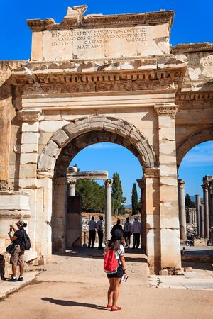 admires: EPHESUS, TURKEY - SEPTEMBER 30, 2014: Woman Tourist with a guide book admires the Gate of Augustus in Efes