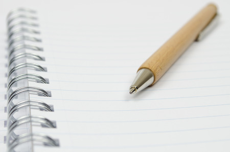 Macro shot of business note-book with a wooden pen