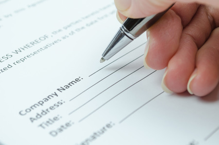 Female hand filling a document with organization name