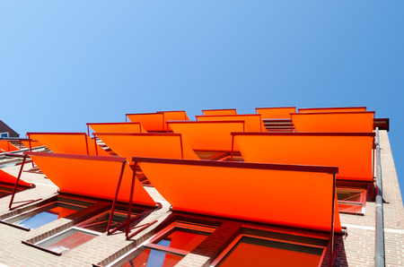 Canopies: Windows at the flats with orange shade sail sun protection. Stock Photo