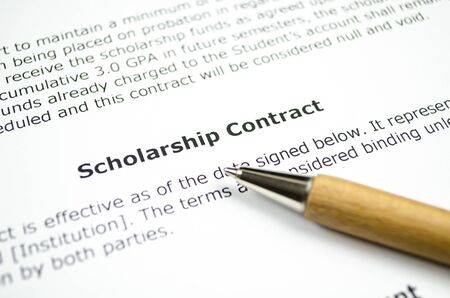 Scholarship contract with wooden pen Stock Photo