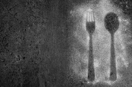 Fork and spoon silhouette on dark