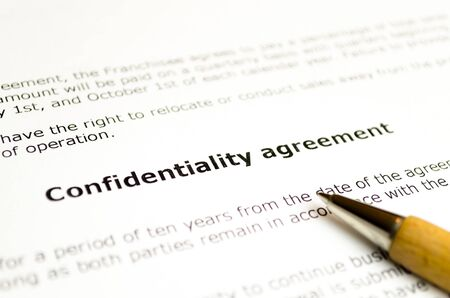 Confidentiality agreement with wooden pen Stock Photo