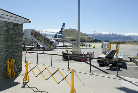 Domestic arrivals sign by Air New Zealand plane, Queenstown airport with mountains in background