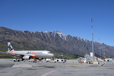 Jetstar plane waiting on the runway at Queenstown airport, Remarkables moutains in the background