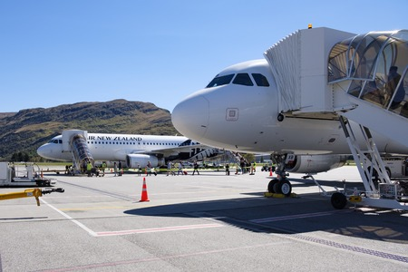 Two Air New Zealand planes with passengers boarding at Queenstown Airport