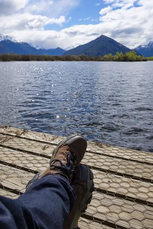 Hiker relaxing on a boardwalk by a lake