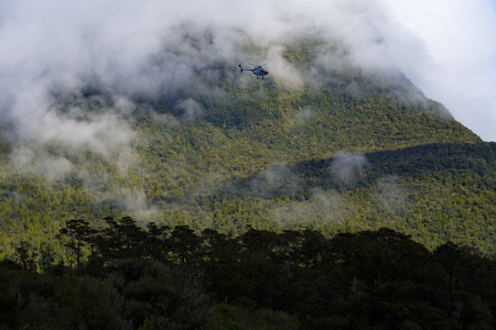 Tourist sightseeing helicopter flight over Milford Sound, New Zealand. Stock Photo