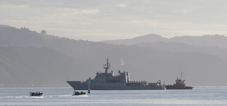 HMNZS Wellington being maneuvered by a tug boat. It's two launches aproach.