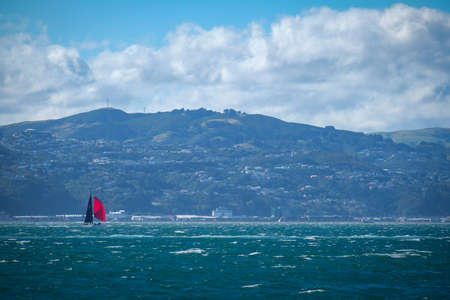 Wellington Harbour, New Zealand 25th April 2021. Yacht with red sail Editorial