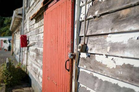 Delapidated building with red door needs some repair Stock Photo