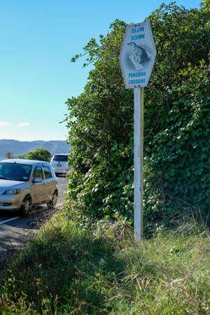 Penguin crossing warning sign near ocean road