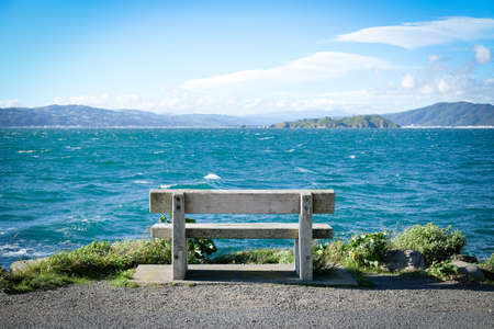 Seascope with solitary wooden bench at ocean edge Stock Photo