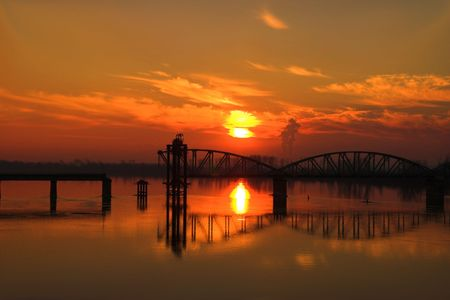 railway river bridge under construction in sunset