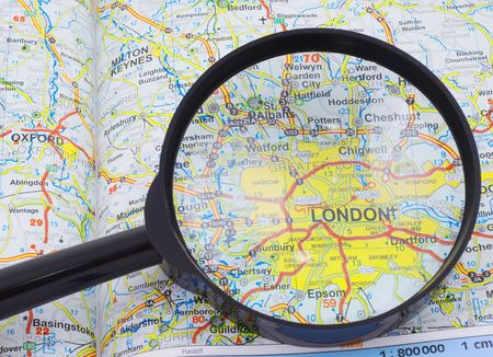 Magnifying glass over the map, focusing on London. photo