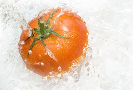 a tomato splashing in water