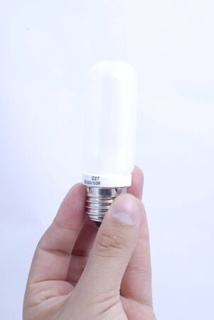 Bulb between the fingers on the white background