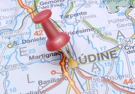 pinpoint: Pin pointing on Udine on Italy map in atlas