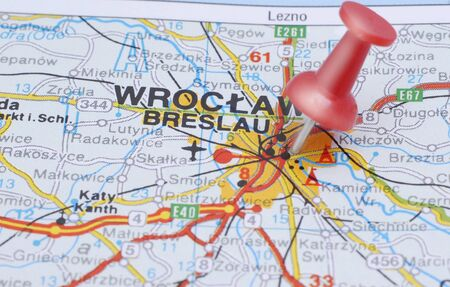 Pin pointing on Wroclaw on Poland map in atlas