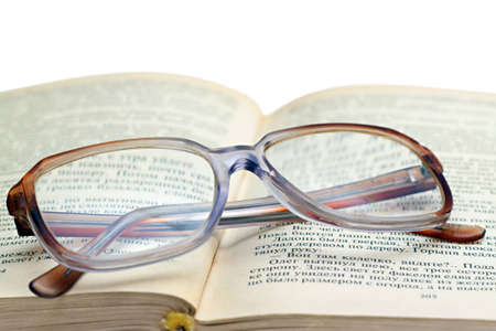reading glasses lying on the book isolated on white photo
