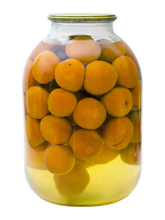 glass jar with a compote of canned apricots isolated on white background photo