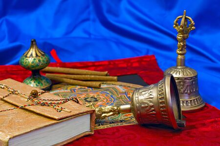 tibet bowls: two Tibetan ritual bell and a book on a blue background Stock Photo