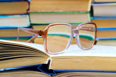 reading glasses lying on the open book Stock Photo - 12931616