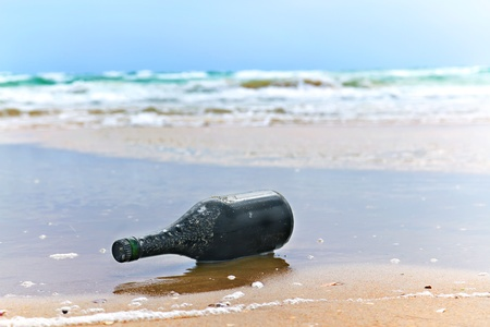 bottle with a note on the sea shore in the background photo