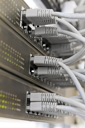 Patch Panel server rack with gray cords in the background Stock Photo