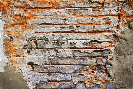 Grunge texture of old brick with plaster falls off in the background photo
