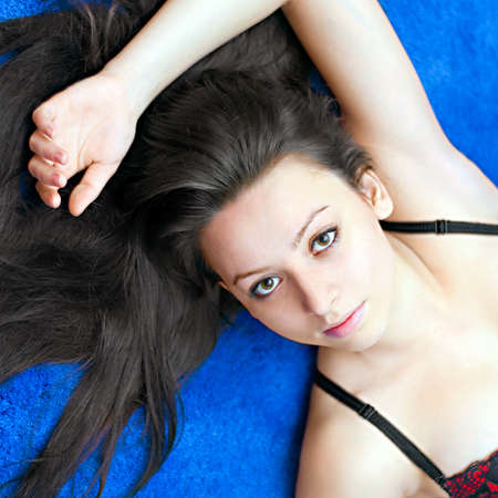 portrait of a young girl lying on  blue background photo