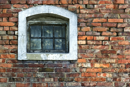 Old brick wall with wooden window in the background in grunge style photo