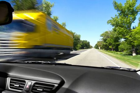Blurred on the speed of the movement of trucks on the road from the window of an oncoming car