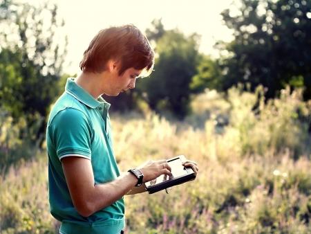 야외에서 태블릿을 가진 젊은 남자 스톡 콘텐츠