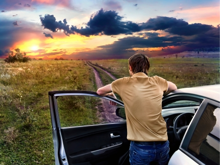 guy is standing near car and looking at the sunset photo