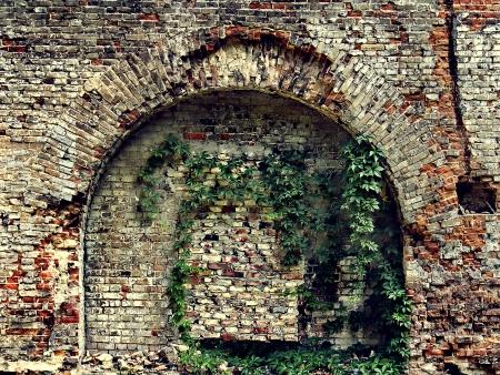crumbling: crumbling stone wall of an old house with brick masonry