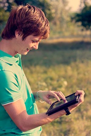 young guy with a tablet outdoors photo