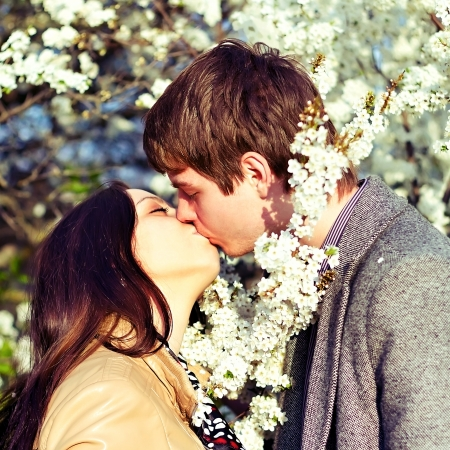 spring outdoor portrait of a young couple kissing photo