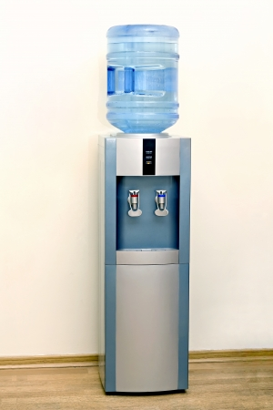 office appliances: Electric water cooler against the background walls of the office