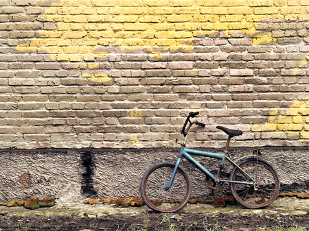 Old rusty vintage bicycle leaning against a brick wall photo