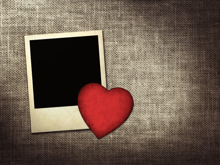 Polaroid-style photo and red paper heart on a linen background photo