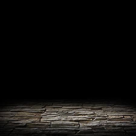 chão de pedra iluminada em um fundo preto Imagens