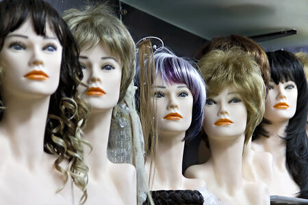 peruke: Several female mannequins with wigs on the shelf