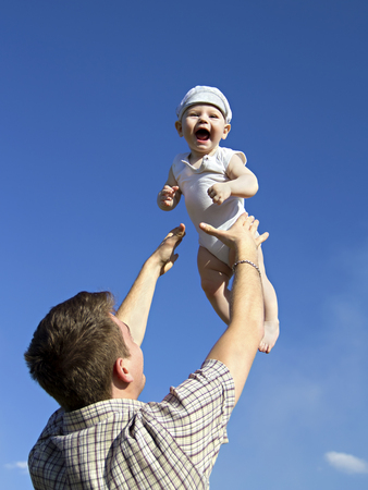 Father tossing baby in the air photo