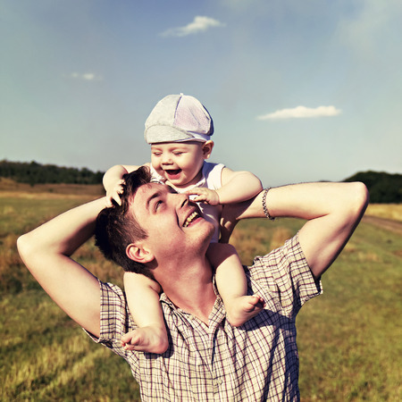 father holds a small child on his shoulders Stock Photo