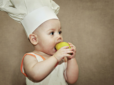 little baby in a chefs hat eating a pear photo