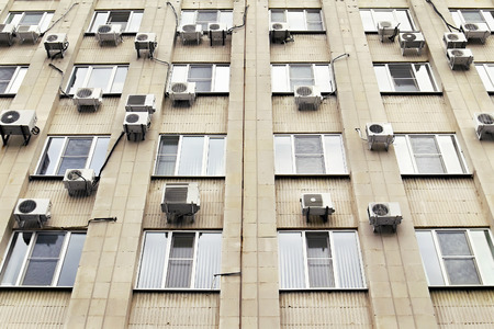 mani air conditioners on the  wall of office building photo