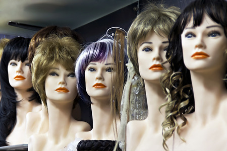 Several female mannequins with wigs on the shelf